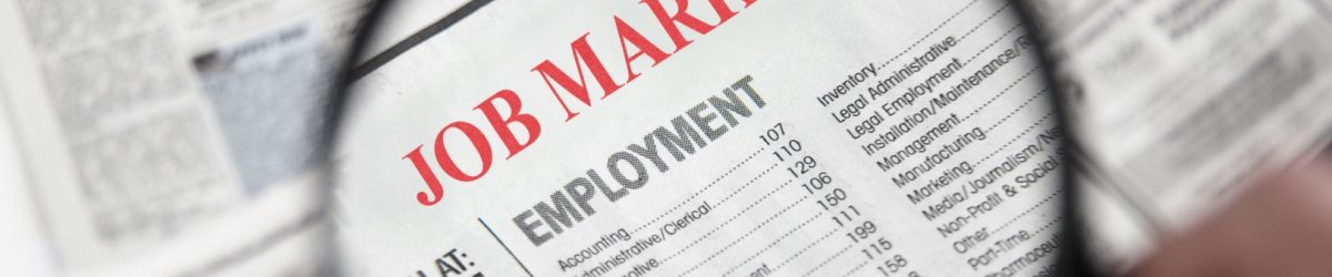Magnifying glass over a newspaper classified section with Job Market text
